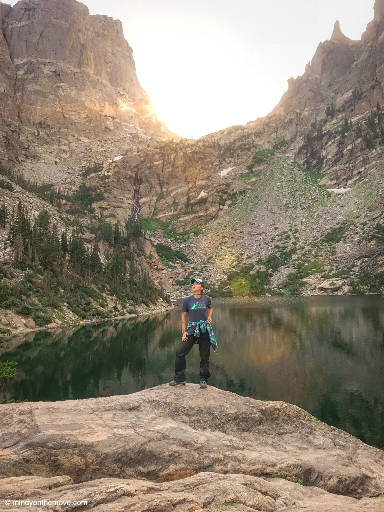 girl hiking to emerald lake in rocky mountain national park at sunset